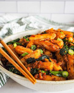 Spicy Vegan Rice Cakes recipe served on a plate with chopsticks.