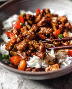 Kung Pao Tempeh recipe displayed in a bowl with chopsticks.