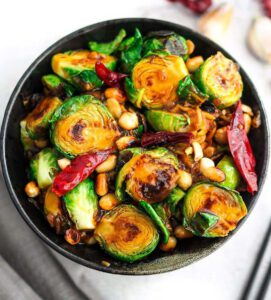Kung Pao Brussels Sprouts recipe served in a bowl with chopsticks.