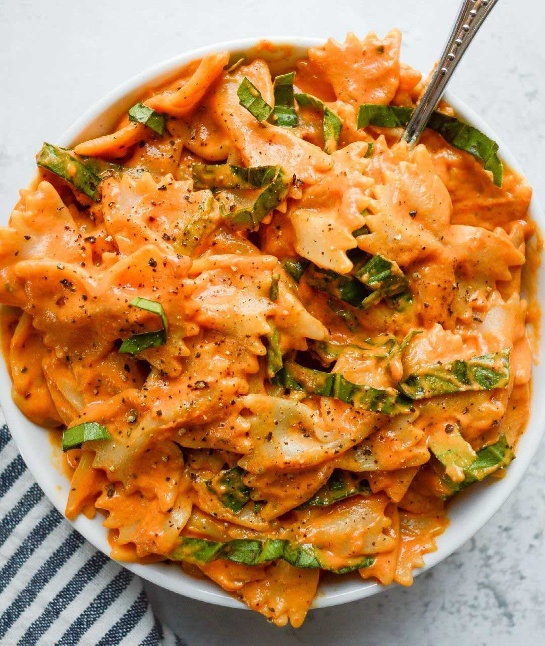 Sun-Dried Tomato and Basil Pasta recipe displayed in a bowl with spoon.
