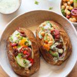 Vegan Mediterranean Stuffed Potatoes With Tzatziki recipe served on a plate.
