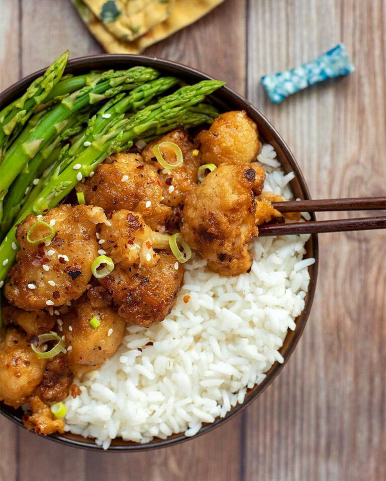 Orange Cauliflower with Steamed Asparagus recipe served in a bowl with chopsticks.